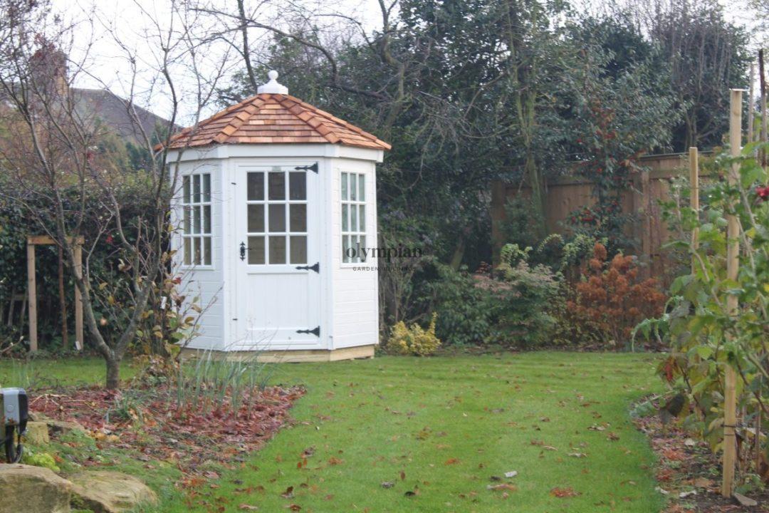 Painted hexagonal summerhouse with cedar shingles